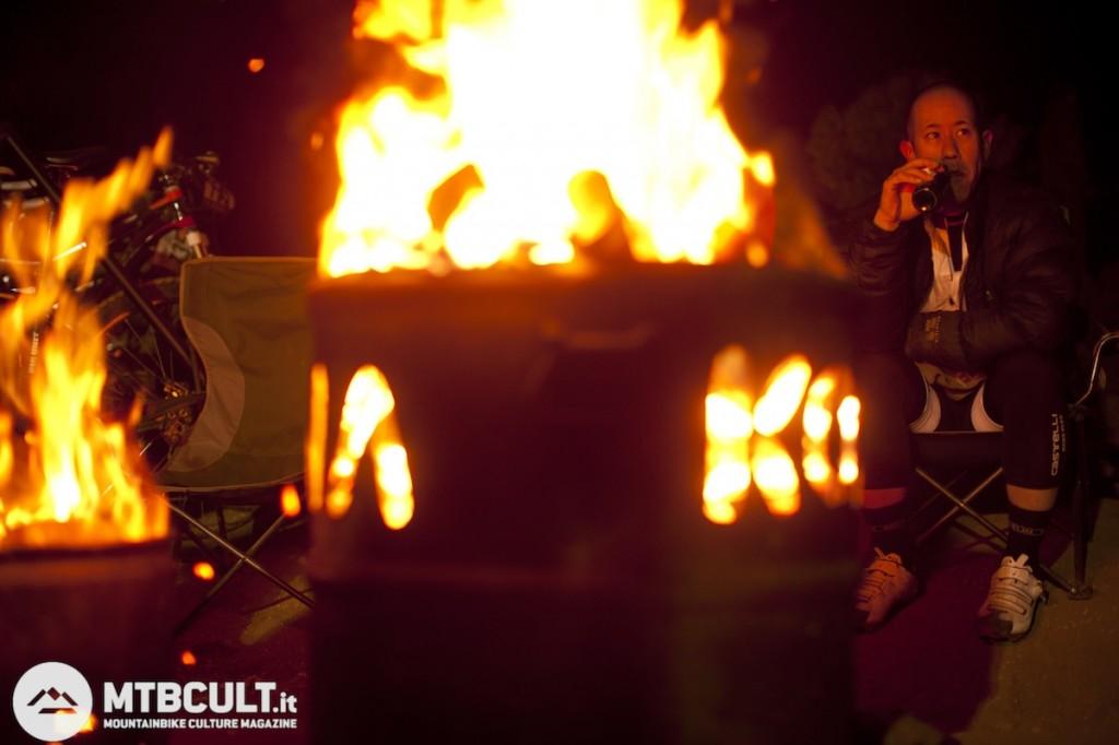 Fra un turno e l'altro ci si scalda davanti al fuoco sorseggiando una birra.